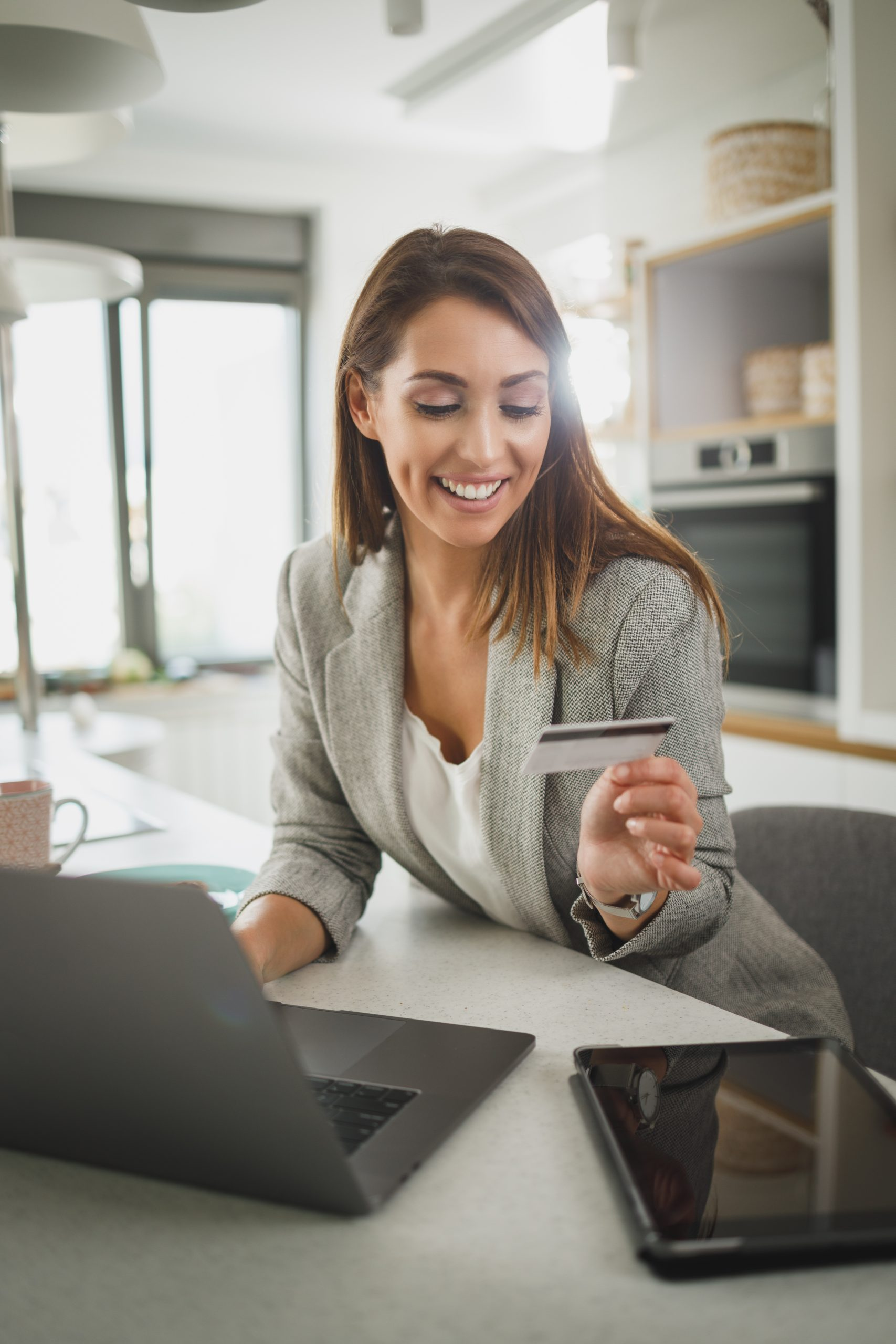 Shot of a young business woman using on her laptop while shopping online in the her kitchen while getting ready to go to work.