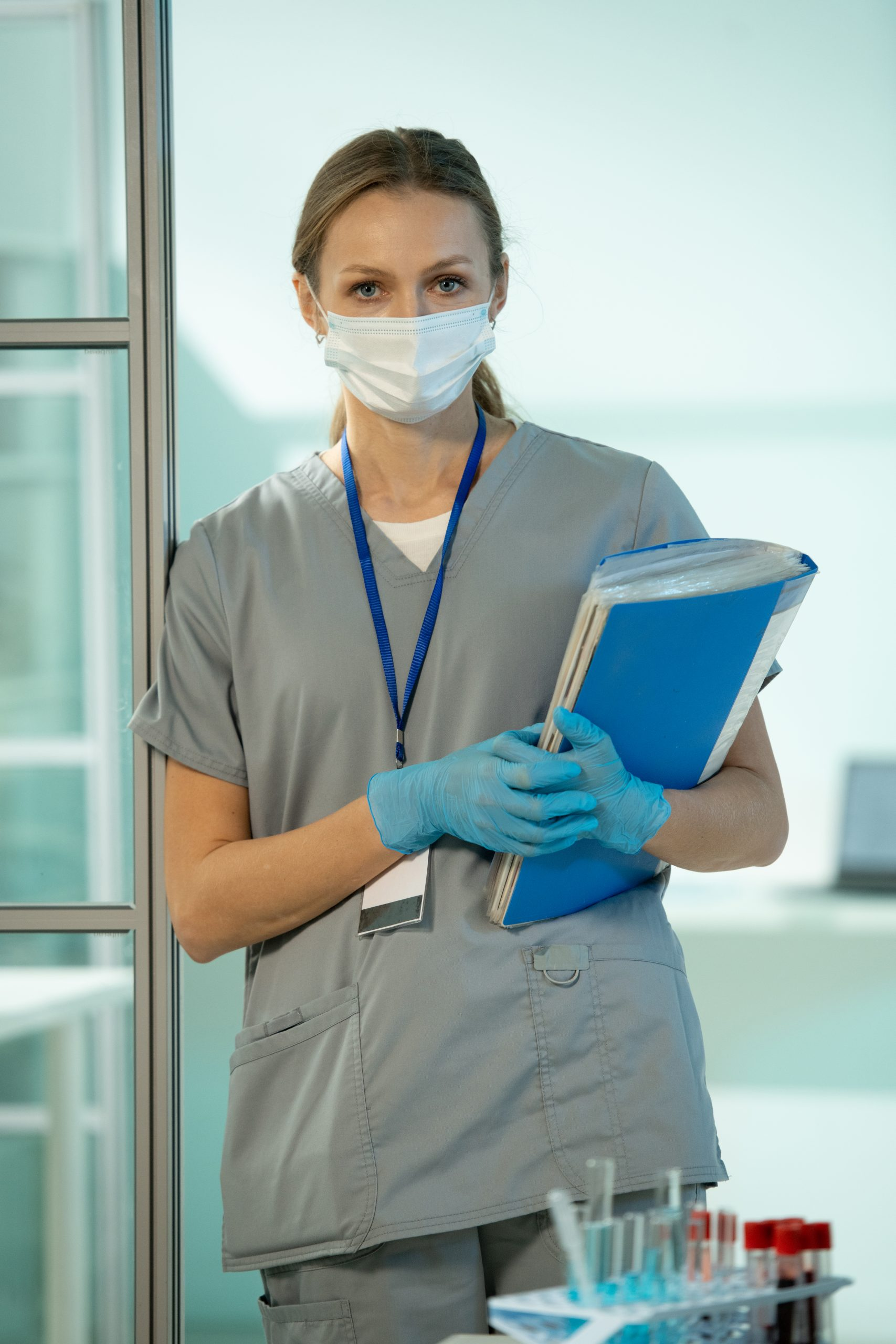 Young serious female clinician in uniform, protective mask and gloves holding medical documents while standing in chemical laboratory